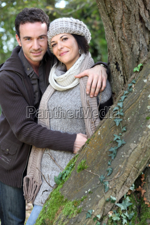 couple stood by tree in park