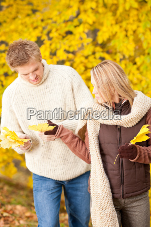 autumn happy couple holding leaves in
