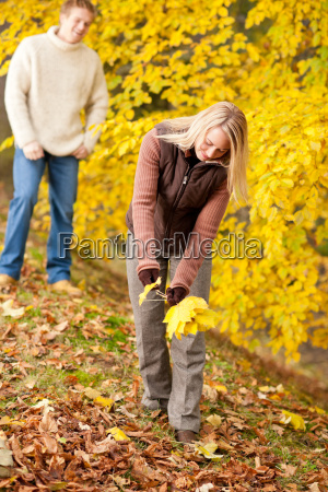 autumn happy couple picking leaves in