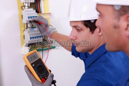 zwei technische ingenieure pruefen elektrischer geraete