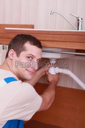 plumber fixing a siphon