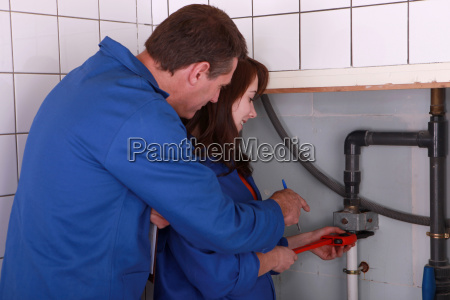 female apprentice plumber and male instructor