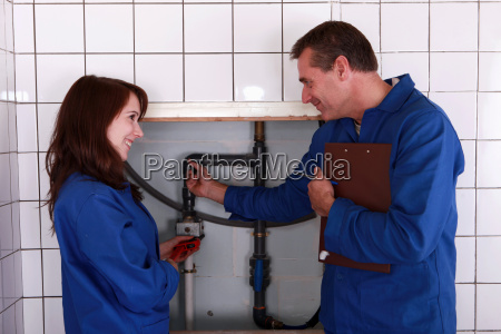 plumber and his apprentice examining the