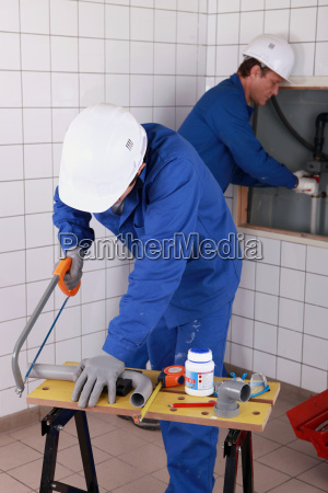 two plumbers working together is bathroom