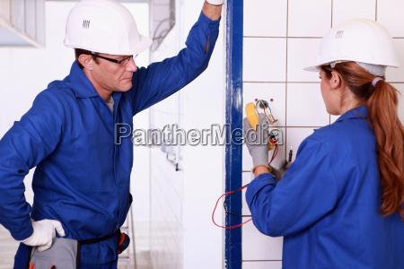 male electrician supervising female apprentice