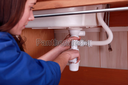 woman fixing the plumbing on a