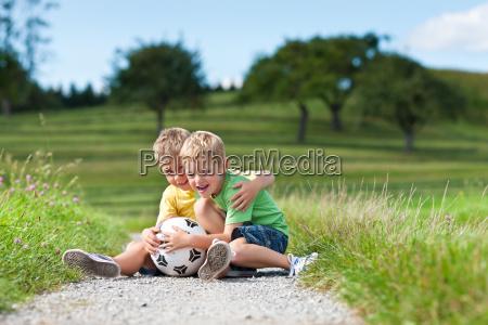due bambini con calcio seduto su