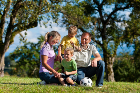 family with children and football on