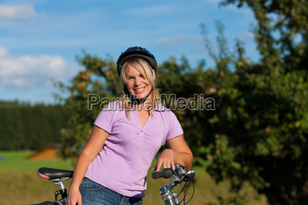 woman with bicycle and helmet
