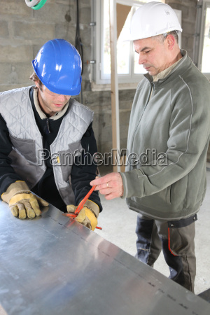 construction workers using a tool