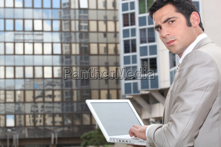 man using his laptop outside an