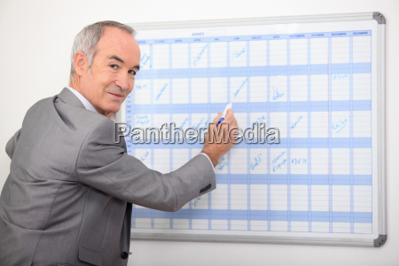 older businessman writing on a wall