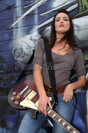 kuehler weiblicher stehen gitarrist gegen graffiti