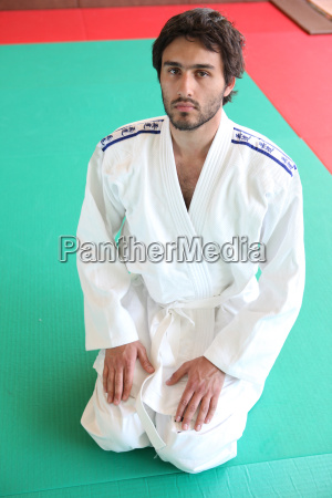 adult male kneeling on mat in