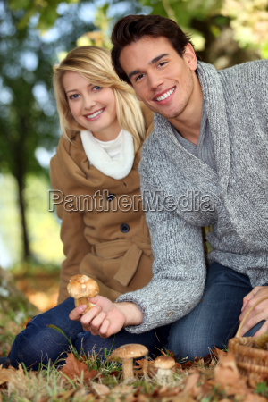 young couple picking mushrooms