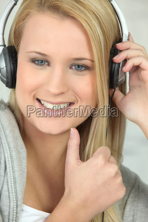 young woman wearing headphones and giving