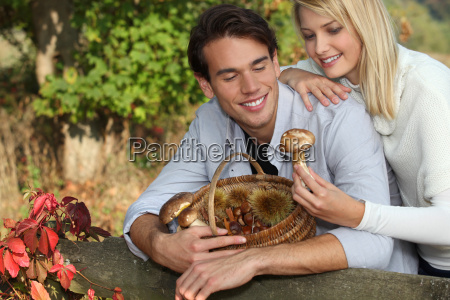 young couple gathering mushrooms