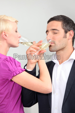 man and woman drinking champagne with