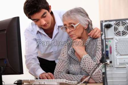 young man showing elderly lady how