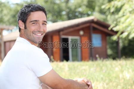 laechelnder mann sitzt vor einer kabine