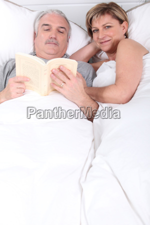 husband reading next to his wife