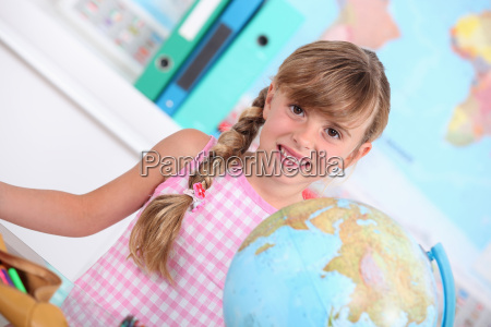 pupil standing behind a globe