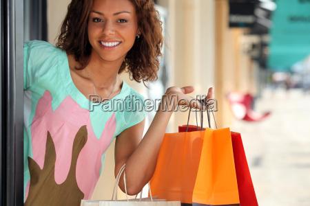 frau verlaesst geschaeft mit einkaufstaschen