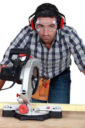 man with goggles using band saw