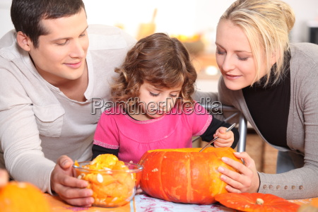 family carving a pumpkin