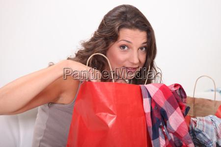 junge frau auf einkaufstueten nach hause