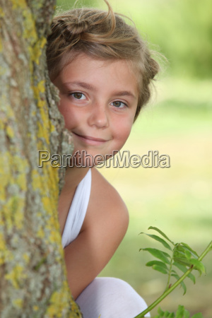 young girl in white dress hiding