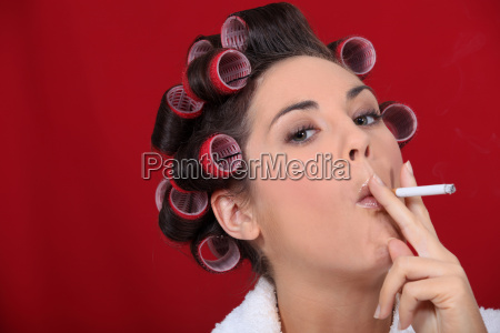woman with hair rollers smoking