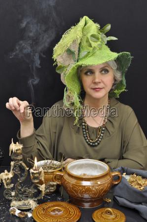 magische frau in gruenem hut mit
