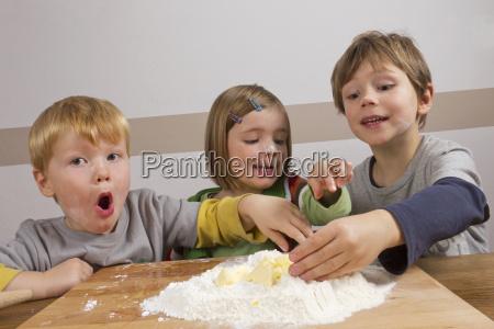 kinder haben spass beim teig kneten