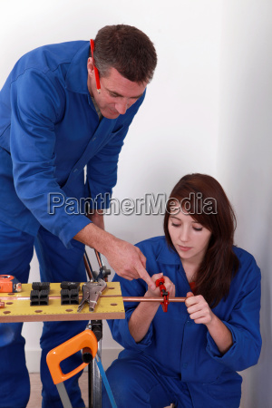 experienced workman showing an apprentice how