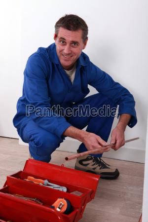 plumber holding length of copper pipe