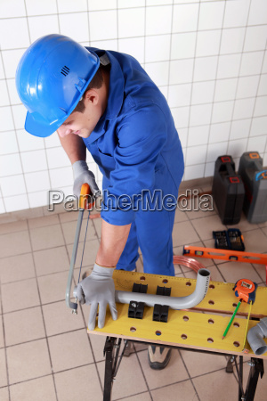 plumber cutting grey plastic pipe
