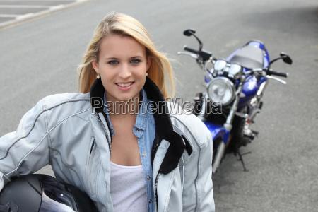 blonde frau stand mit dem motorrad