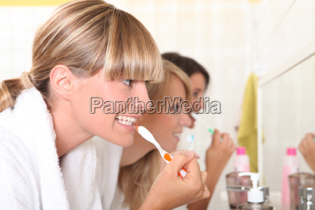 drei junge damen ihre zaehne putzen