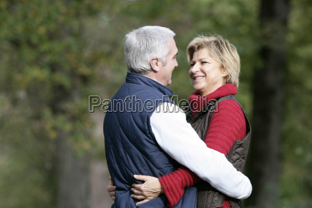 married couple hugging in park