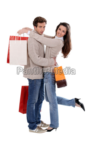 paar mit einkaufstueten umarmt