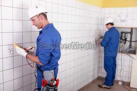 workteam installation elektrik in einem gekachelten