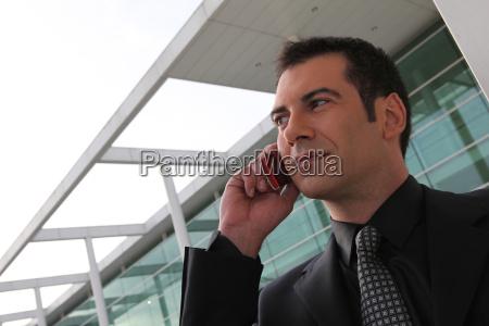 businessman stood outside office telephoning
