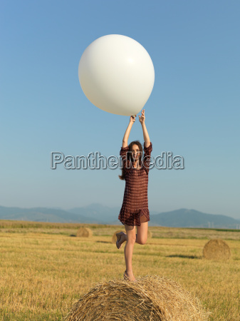 happy woman jumping white balloon hay