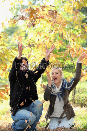 couple playing with autumn leaves