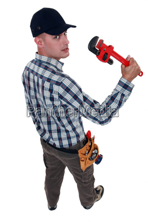 worker with an adjustable pipe wrench