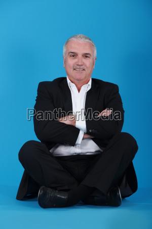mature man sitting cross legged and