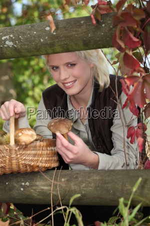 woman picking mushrooms in the woods