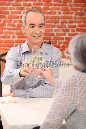 senior couple drinking champagne in a