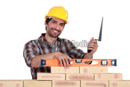 a mason checking a wall with